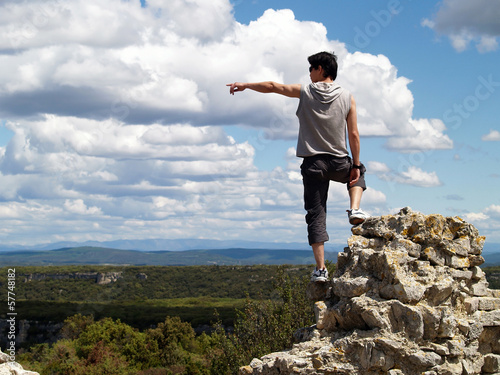 Hiker standing near the edge of a cliff pointing somethng