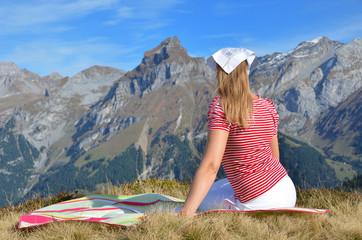 Young woman having rest in Alpine meadow. Switzerland