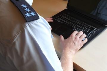 Polizei im Büro am Computer