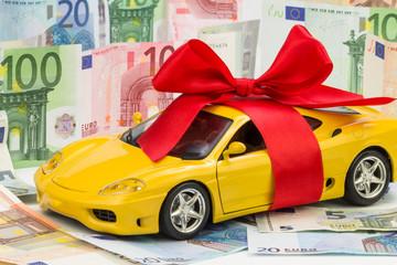 gelbes Auto mit roter Schleife und Geldscheine