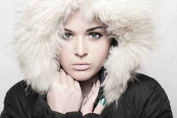 Fashion portrait of young beautiful woman with fur. hood