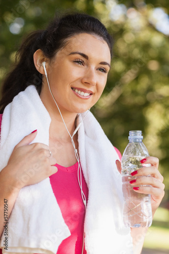 Happy sporty woman wearing sportswear holding a bottle