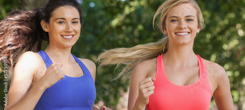 Two cute sporty women running in a park