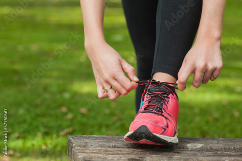 Young woman tying the shoelaces of her running shoes