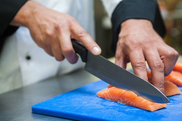 Close up of chef slicing salmon with sharp knife