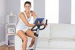 Cheerful sporty woman training on an exercise bike while holding