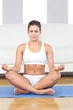 Pretty sporty woman in sportswear sitting on an exercise mat in