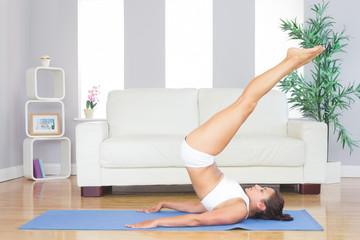 Young cute woman practicing yoga pose on a blue exercise mat