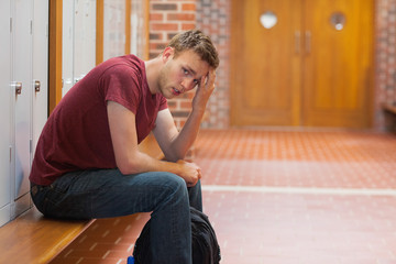 Frowning handsome student having a headache