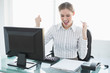 Happy chic businesswoman sitting at her desk in front of her com