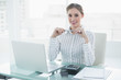 Cheerful lovely businesswoman sitting at her desk holding a penc