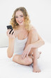 Pretty smiling blonde sitting on bed holding smartphone
