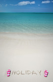 HOLIDAY writing on the sandy beach of Exuma, Bahamas