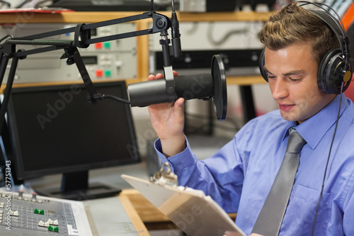 Well dressed focused radio host moderating