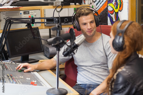 Attractive content radio host interviewing a guest - 57751344