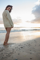 Full length of a woman in sweater standing on beach
