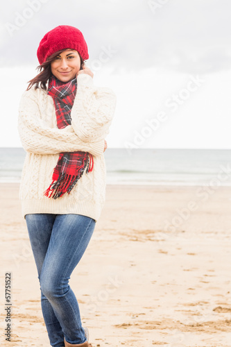 Cute smiling woman in stylish warm clothing at beach