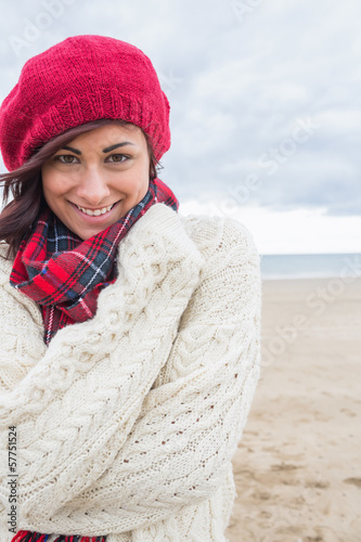 Cute smiling woman in stylish warm clothing on the beach