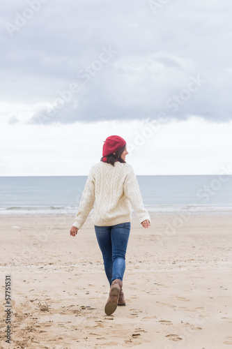 Rear view of a woman in stylish warm wear on beach