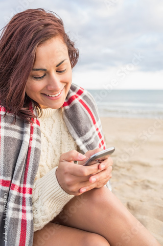 Smiling woman covered with blanket using cellphone at beach