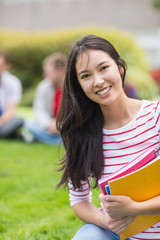 Smiling college student with blurred friends in park
