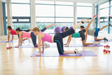 Fotoroleta Side view of women stretching on mats at yoga class