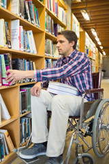 Man in wheelchair selecting book in library