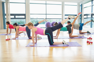 Side view of women stretching on mats at yoga class