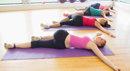 Sporty people stretching on mats at yoga class