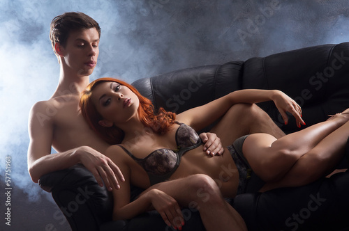 A beautiful couple hugging on a leather sofa at night