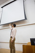 Teacher with projection screen in the lecture hall
