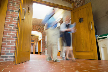 Group of blurred people walking through open doors
