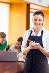 Waitress writing an order with students using laptop at  coffee
