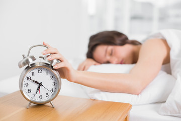 Sleepy blurred woman in bed extending hand to alarm clock