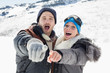 Couple in jackets pointing at the camera on snow covered landsca