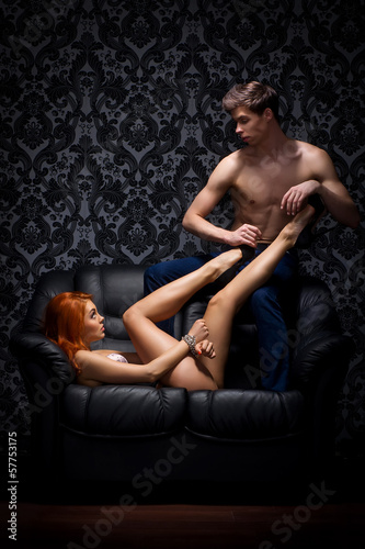 A young and beautiful couple relaxing on a leather sofa