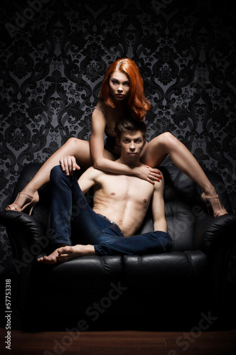 A young and beautiful couple on a leather sofa