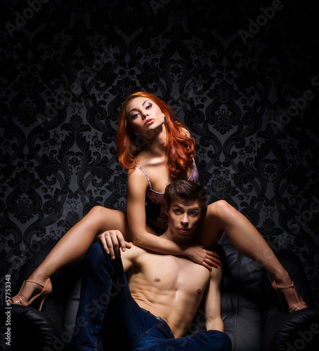 A young and beautiful couple playing on a leather sofa