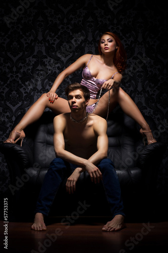 A young couple in bdsm action on the leather sofa