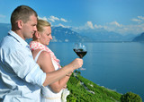 Man and woman tasting wine among vineyards in Lavaux, Switzerlan