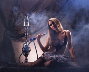 A sexy woman in a luxury underwear smoking a hookah
