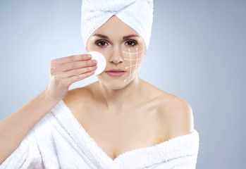 A young and healthy woman in a towel pampering her face