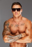 Handsome man in sunglasses with muscular tattooed torso