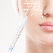Beautiful face and the syringe (plastic surgery concept)