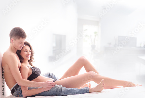 A young and loving couple relaxing on a light background