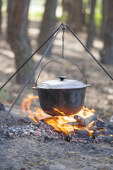 Camping kettle over burning campfire.