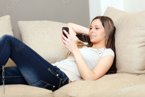 Woman lying on the couch and texting with her smartphone