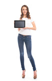 A young girl in stylish jeans holding a tablet computer