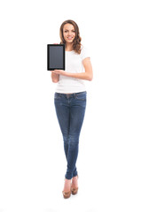 A happy girl in stylish jeans holding a tablet computer