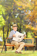 Senior gentleman seated on a bench reading a newspaper in a park